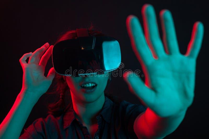 Aantrekkelijke jonge vrouw die haar virtuele werkelijkheidsbeschermende brillen in studio met gekleurde verlichting aanpassen stock foto
