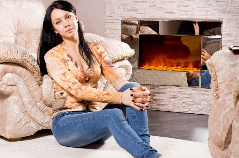 Het ontspannen van de vrouw voor een warme brand stock foto's