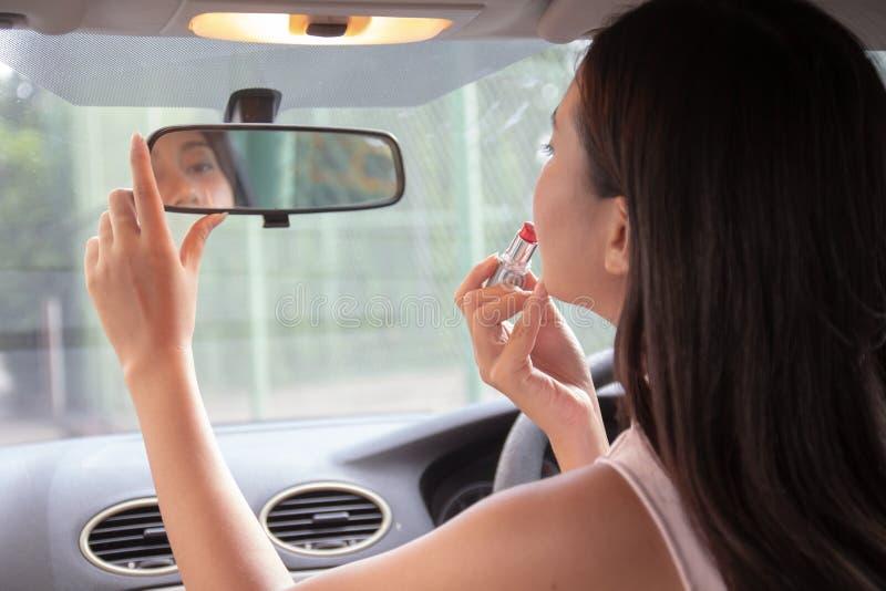 Aantrekkelijke jonge vrouw die lippenstift toepassen die spiegel in auto bekijken Het meisje past haar make-up aan zettend lippen stock afbeelding