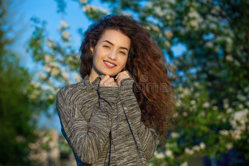 Aantrekkelijke jonge vrouw die met krullend haar op de achtergrond van mooie bloeiende boom glimlachen stock fotografie