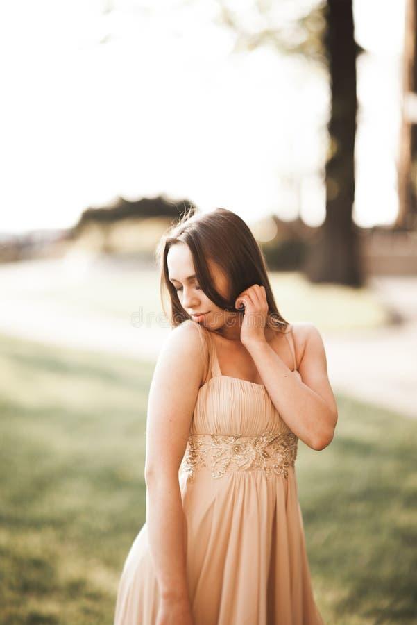 Aantrekkelijke jonge vrouw die met lange kleding van haar tijd buiten op de achtergrond van de parkzonsondergang genieten royalty-vrije stock foto