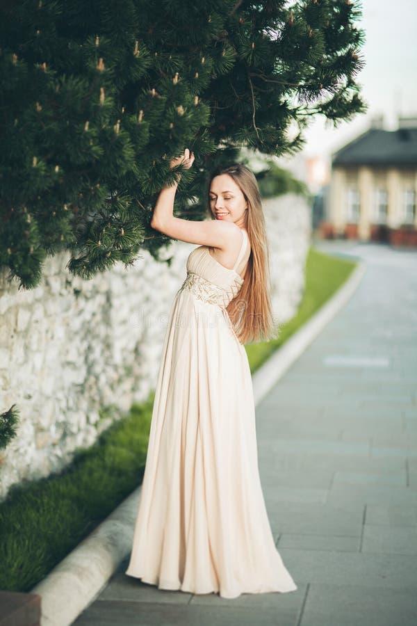 Aantrekkelijke jonge vrouw die met lange kleding van haar tijd buiten op de achtergrond van de parkzonsondergang genieten royalty-vrije stock afbeeldingen