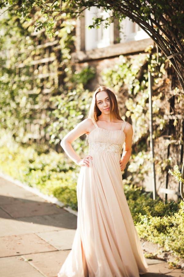 Aantrekkelijke jonge vrouw die met lange kleding van haar tijd buiten op de achtergrond van de parkzonsondergang genieten stock afbeelding