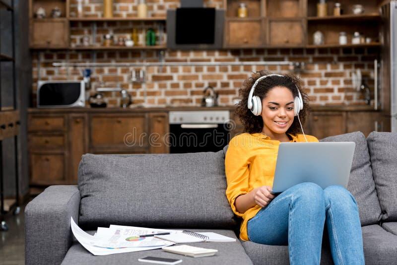 aantrekkelijke jonge vrouw die met laptop en het luisteren muziek werken royalty-vrije stock foto