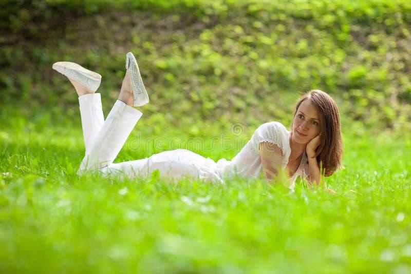 Aantrekkelijke jonge vrouw die op groen gras liggen royalty-vrije stock afbeeldingen