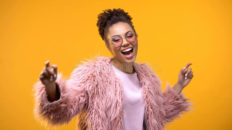 Aantrekkelijke jonge vrouw die op heldere achtergrond dansen, die tot muziek, plezier leiden stock foto's