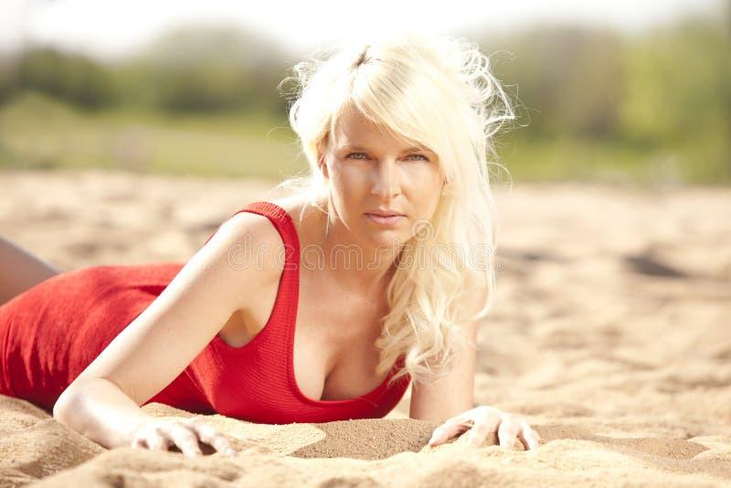 Aantrekkelijke jonge vrouw die op het strand liggen royalty-vrije stock foto
