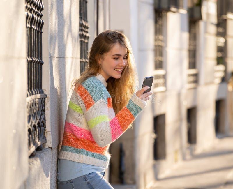Aantrekkelijke jonge vrouw die op smartphone sociale media mobiele toepassingen buiten stad controleren royalty-vrije stock afbeeldingen
