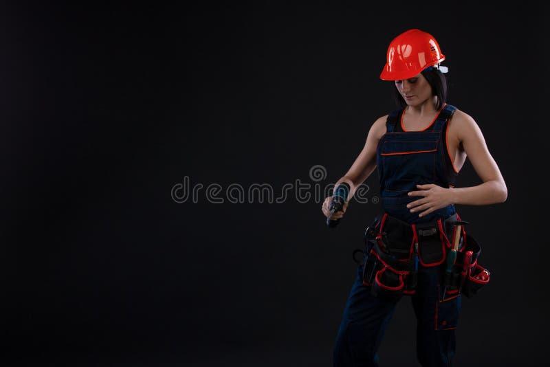 Aantrekkelijke jonge vrouw die reparaties doen bij zwarte achtergrond Portret van een vrouwelijke bouwvakker De bouw, reparatieco royalty-vrije stock afbeelding