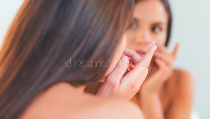 Download Aantrekkelijke Jonge Vrouw Die Room Op Haar Gezicht Toepassen Stock Foto - Afbeelding bestaande uit teint, huid: 107704918