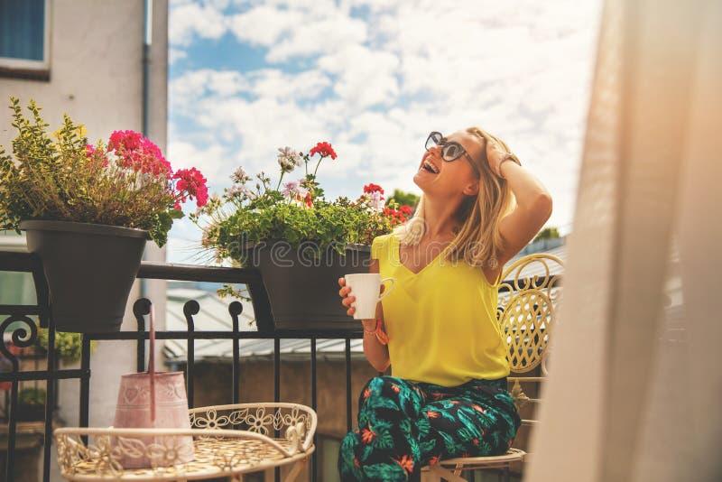 Aantrekkelijke jonge vrouw die van vakanties genieten en koffie op hotelbalkon drinken stock afbeeldingen
