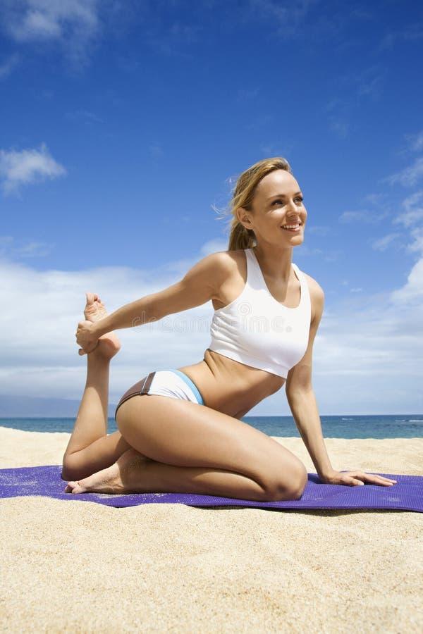 Aantrekkelijke Jonge Vrouw die Yoga op Strand doet stock fotografie
