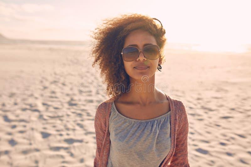 Aantrekkelijke jonge vrouw die zich op een strand bevinden stock foto