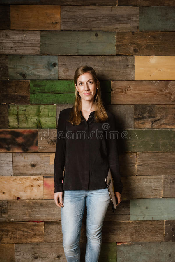 Aantrekkelijke jonge vrouw die zich tegen een houten muur in bureau bevinden royalty-vrije stock afbeeldingen