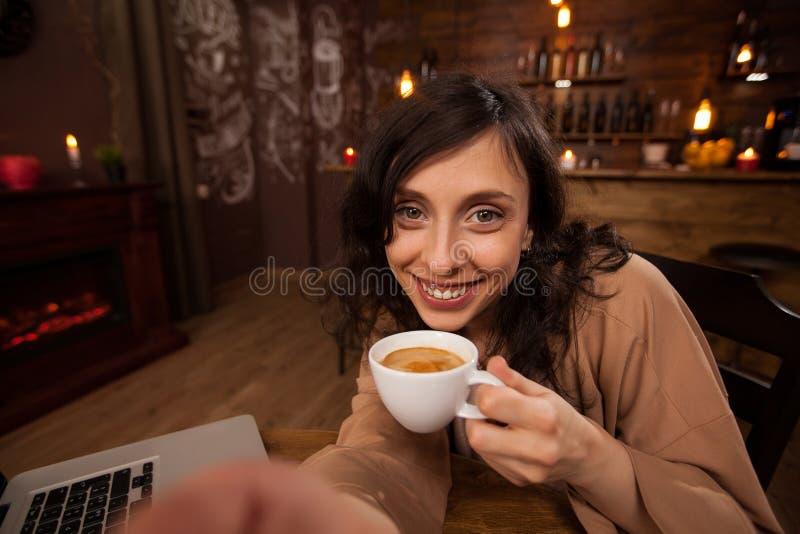 Aantrekkelijke jonge vrouw een camera en een kop die van koffie nemend een selfie houden stock foto