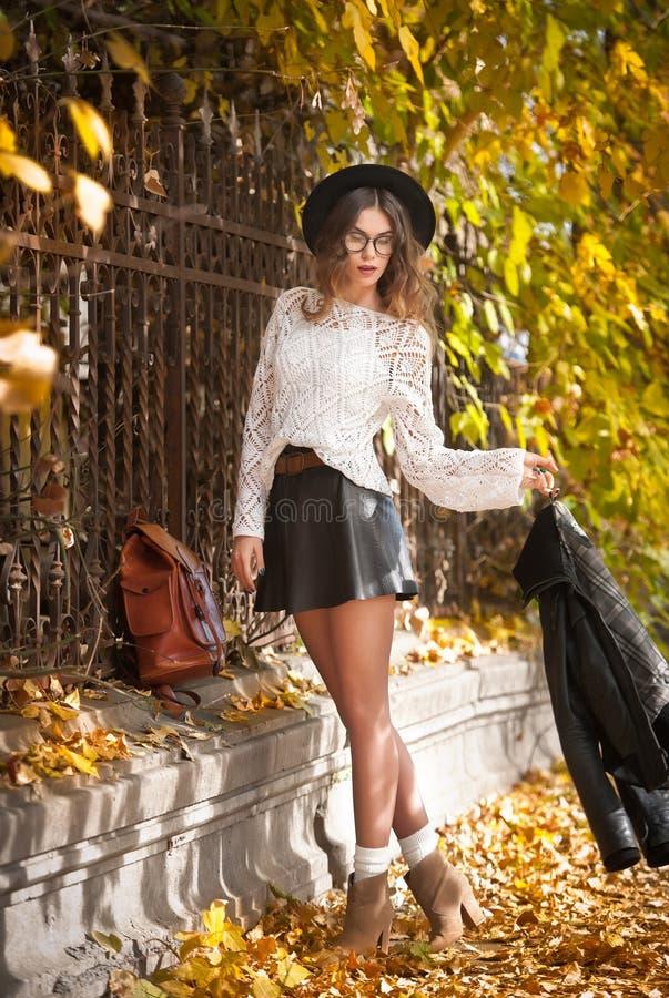 Aantrekkelijke jonge vrouw in een herfstschot in openlucht Het mooie modieuze schoolmeisje stellen in park met langzaam verdwenen royalty-vrije stock foto