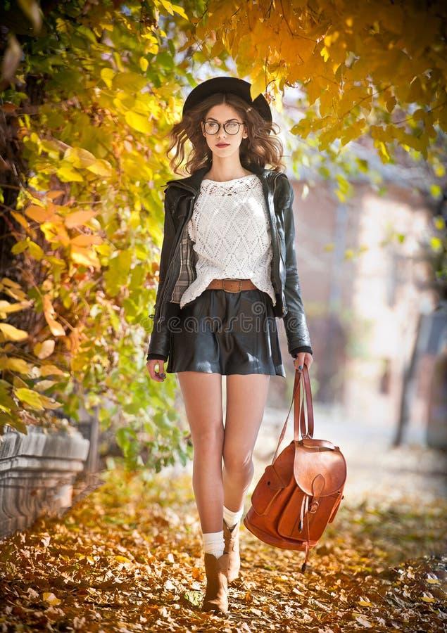 Aantrekkelijke jonge vrouw in een herfstschot in openlucht Het mooie modieuze schoolmeisje stellen in park met langzaam verdwenen stock foto