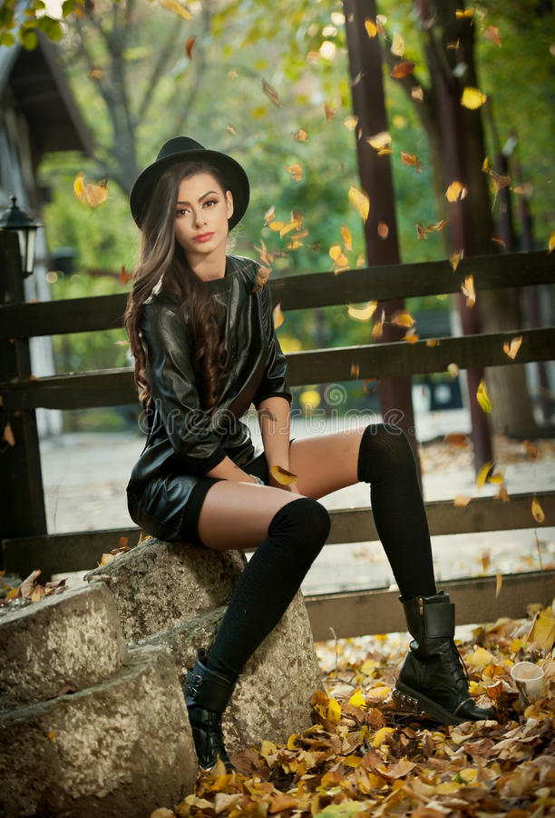 Aantrekkelijke jonge vrouw in een herfstschot, in openlucht Mooi modieus meisje met moderne uitrustings stellende zitting in park stock afbeelding