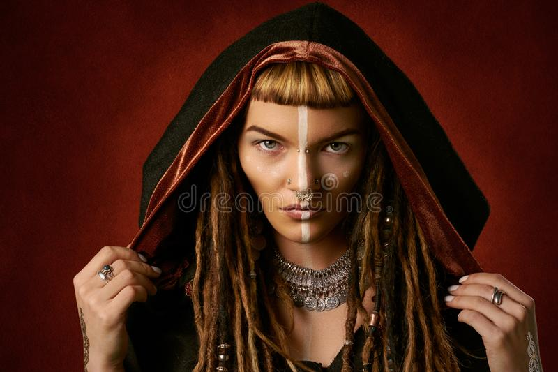 Aantrekkelijke jonge vrouw in een stammenkostuum op rode achtergrond stock afbeelding
