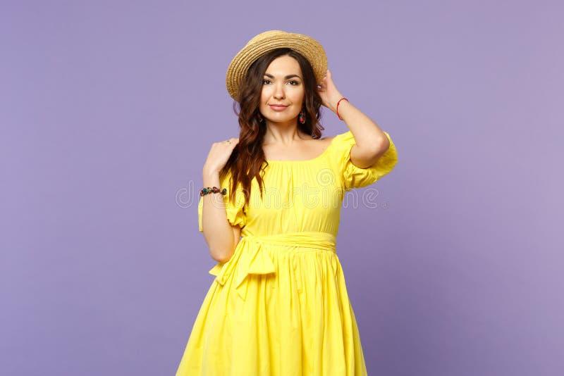 Aantrekkelijke jonge vrouw in gele kleding die hand op de zomerhoed houden die camera geïsoleerd op pastelkleur violette muur kij stock fotografie