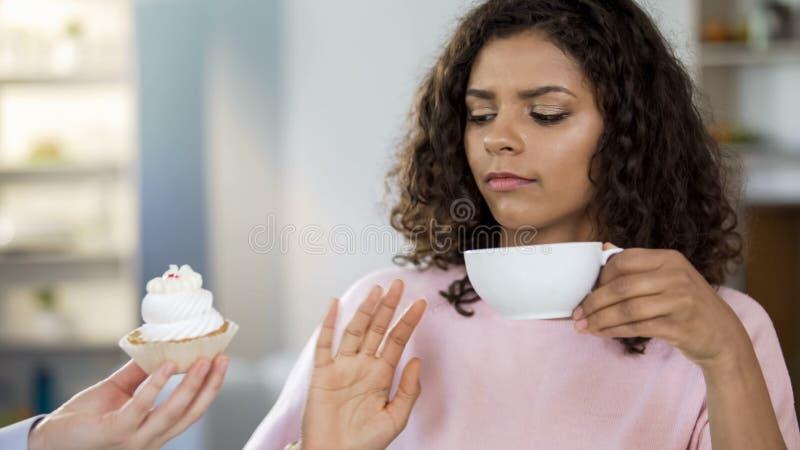 Aantrekkelijke jonge vrouw het drinken thee, die nr aan room-cake, het gezonde op dieet zijn zeggen royalty-vrije stock foto's