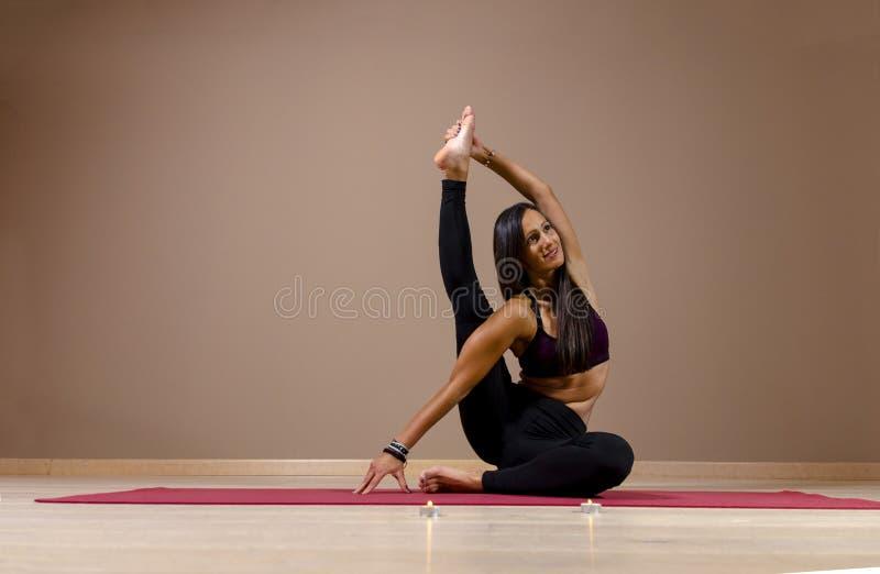 Aantrekkelijke jonge vrouw het praktizeren yoga binnen royalty-vrije stock foto