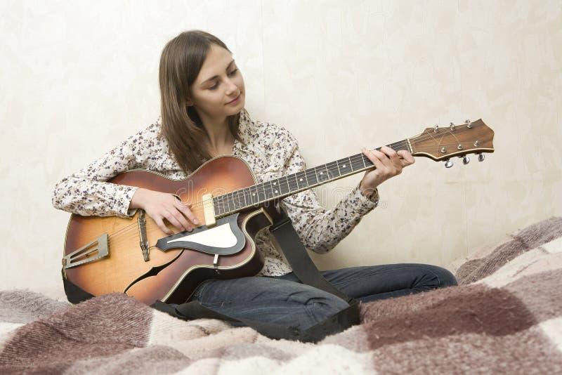 Aantrekkelijke jonge vrouw het spelen gitaar stock foto