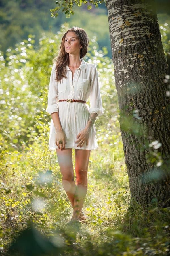 Aantrekkelijke jonge vrouw in het witte korte kleding stellen dichtbij een boom in een zonnige de zomerdag Mooi meisje dat van de royalty-vrije stock afbeeldingen