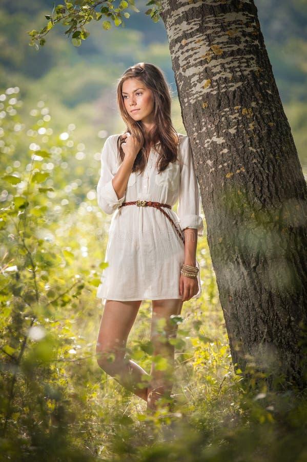 Aantrekkelijke jonge vrouw in het witte korte kleding stellen dichtbij een boom in een zonnige de zomerdag Mooi meisje dat van de stock foto