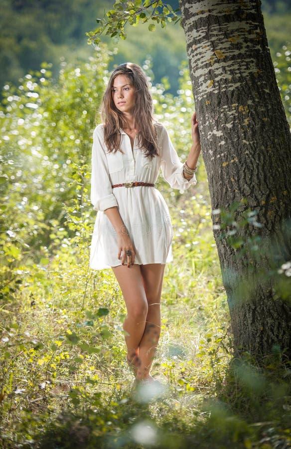 Aantrekkelijke jonge vrouw in het witte korte kleding stellen dichtbij een boom in een zonnige de zomerdag Mooi meisje dat van de stock foto's
