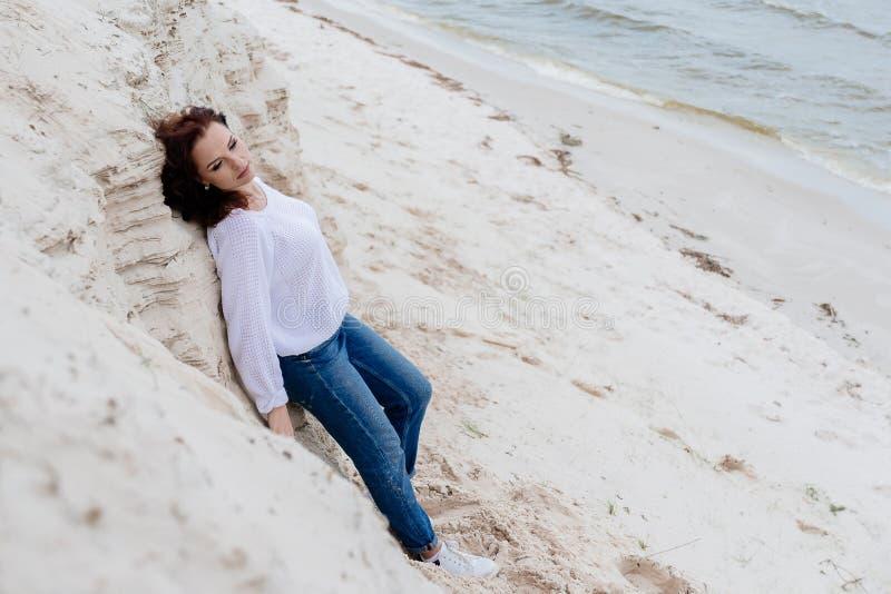Aantrekkelijke jonge vrouw im warme doek op het strand in koud weer royalty-vrije stock afbeeldingen