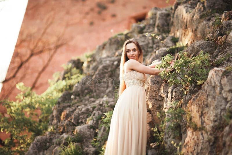 Aantrekkelijke jonge vrouw in lange kleding die zich op de rotsen bevinden royalty-vrije stock fotografie