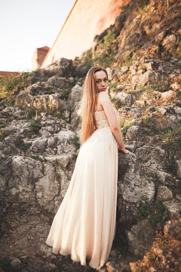 Aantrekkelijke jonge vrouw in lange kleding die zich op de rotsen bevinden royalty-vrije stock foto's