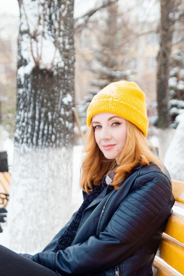 Aantrekkelijke jonge vrouw met blauwe ogen en blond haar in een gele het breien hoedenzitting op een gele bank in het de winterpa royalty-vrije stock foto