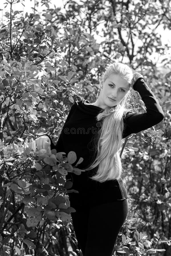 Aantrekkelijke jonge vrouw met het lange mooie haar het glimlachen in openlucht stellen Zwarte, witte foto stock afbeeldingen
