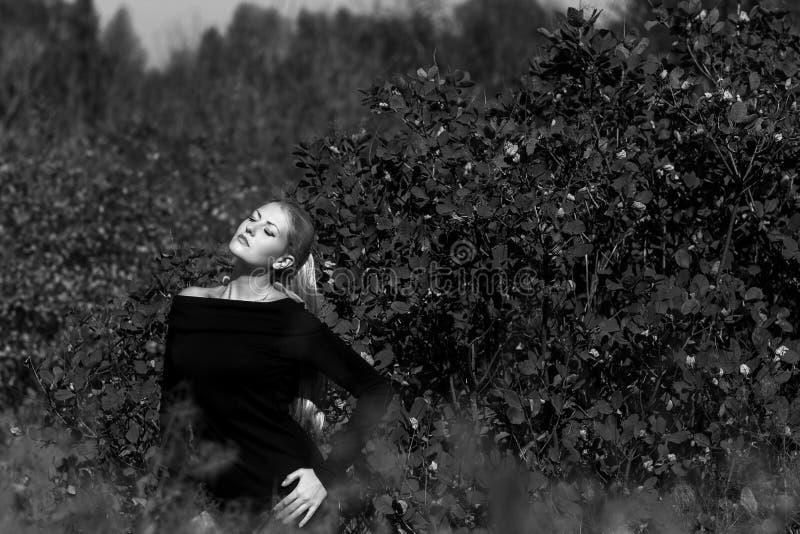 Aantrekkelijke jonge vrouw met het lange mooie haar het glimlachen in openlucht stellen Zwarte, witte foto stock foto