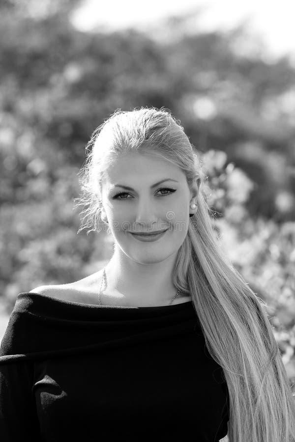 Aantrekkelijke jonge vrouw met het lange mooie haar glimlachen stellend o royalty-vrije stock afbeelding