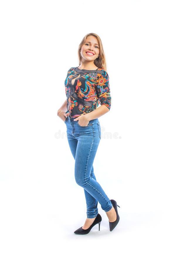 Aantrekkelijke jonge vrouw met lang blond haar in jeans, een blouse en schoenen die bij de camera in profiel met haar handen stel royalty-vrije stock foto's