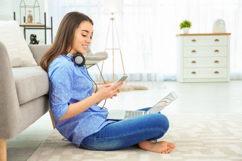 Aantrekkelijke jonge vrouw met mobiele telefoon op vloer royalty-vrije stock fotografie