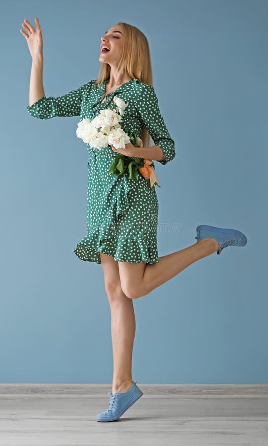 Aantrekkelijke jonge vrouw met mooie bloemen dichtbij kleurenmuur royalty-vrije stock foto