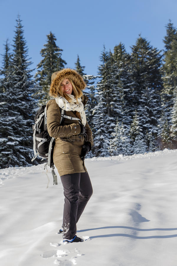 Aantrekkelijke Jonge Vrouw met Rugzak op Sneeuw Wandelingssleep, die bij Camera glimlachen royalty-vrije stock foto's