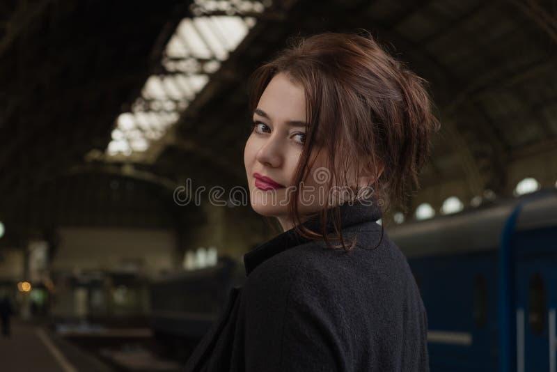 Aantrekkelijke jonge vrouw millenial in zwarte kleren en een hoed en glazen bij het station naast de trein royalty-vrije stock foto's