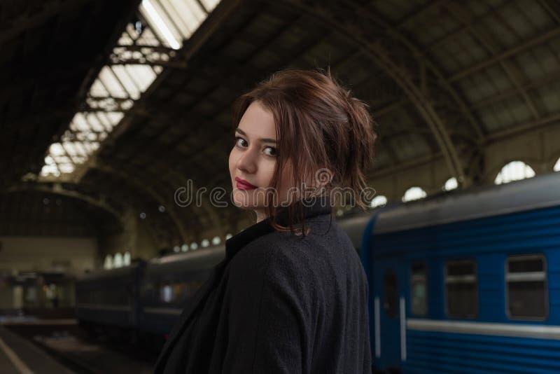 Aantrekkelijke jonge vrouw millenial in zwarte kleren en een hoed en glazen bij het station naast de trein royalty-vrije stock afbeeldingen