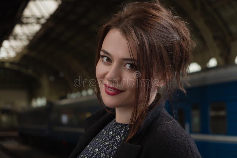 Aantrekkelijke jonge vrouw millenial in zwarte kleren en een hoed en glazen bij het station naast de trein royalty-vrije stock foto
