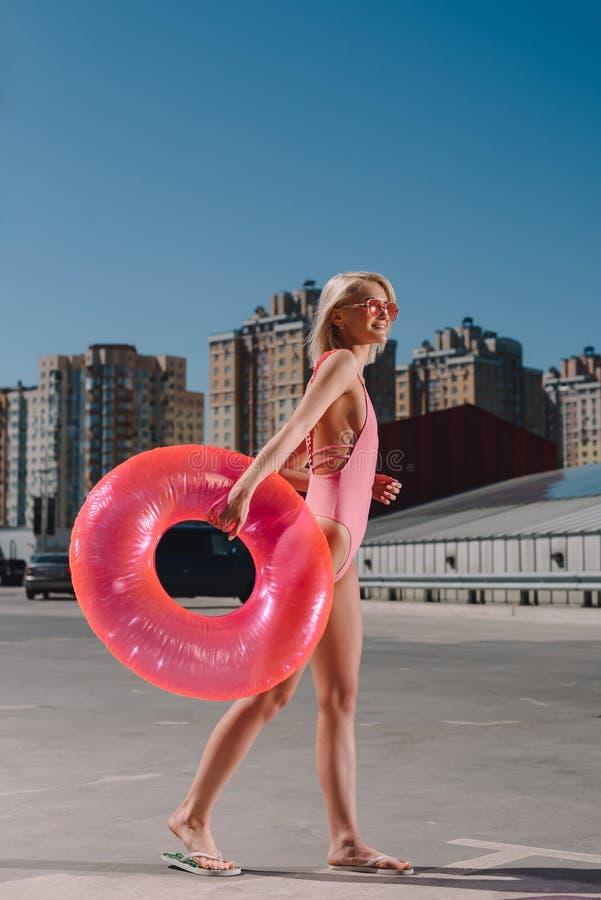 aantrekkelijke jonge vrouw in modieus roze zwempak met opblaasbare ring stock afbeelding
