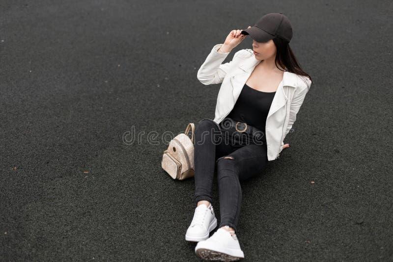 Aantrekkelijke jonge vrouw in modieuze gescheurde jeans in een leerjasje in een t-shirt met een gouden rugzak in modieuze tenniss royalty-vrije stock foto