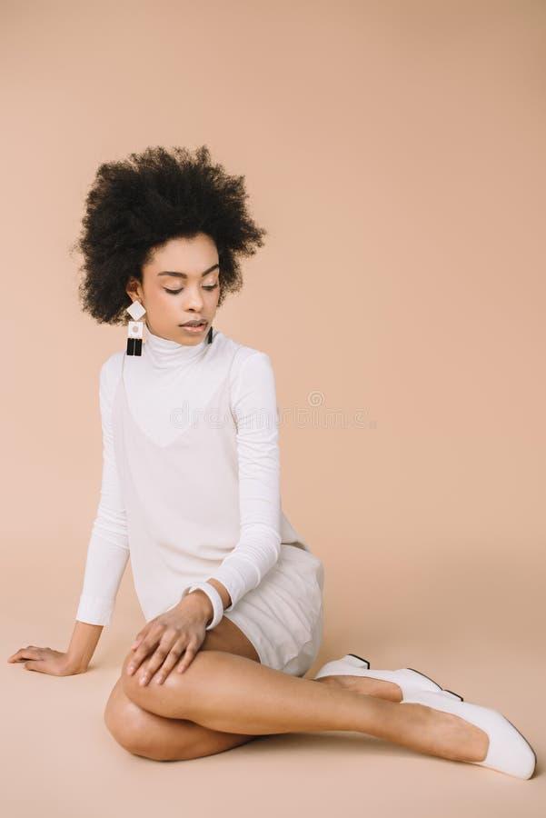aantrekkelijke jonge vrouw in modieuze witte kleding en schoenen die op vloer zitten stock afbeelding