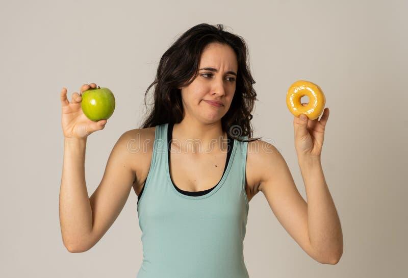 Aantrekkelijke jonge vrouw op een dieet die tussen een appel en een doughnut beslissen stock foto
