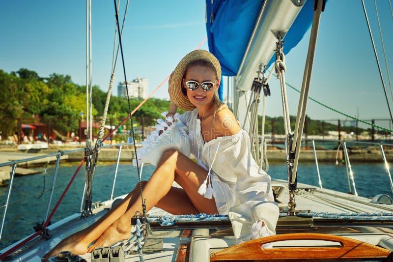 Aantrekkelijke jonge vrouw op een jacht op een de zomerdag royalty-vrije stock afbeelding