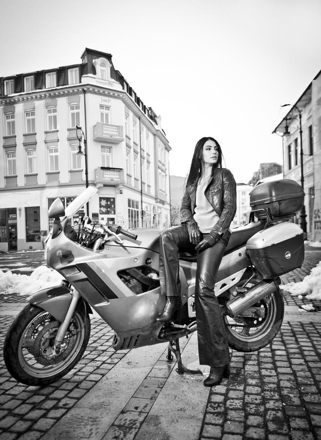 Aantrekkelijke jonge vrouw op stedelijke die manier dichtbij motorfiets wordt geschoten Mooi modieus jong meisje in zwarte leerui royalty-vrije stock foto